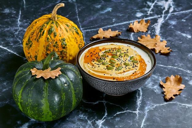 黄色いオークの葉と有機カボチャの暗い大理石のテーブルに対してボウルにクリームとクリーミーなカボチャのスープ