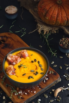 검은 나무 테이블에 검은 그릇에 크림과 호박 씨앗과 볶은 베이컨 조각으로 크림 호박 수프. 상위 뷰, 선택적 초점. 테이블에 계절 호박 수프를 만들기위한 재료