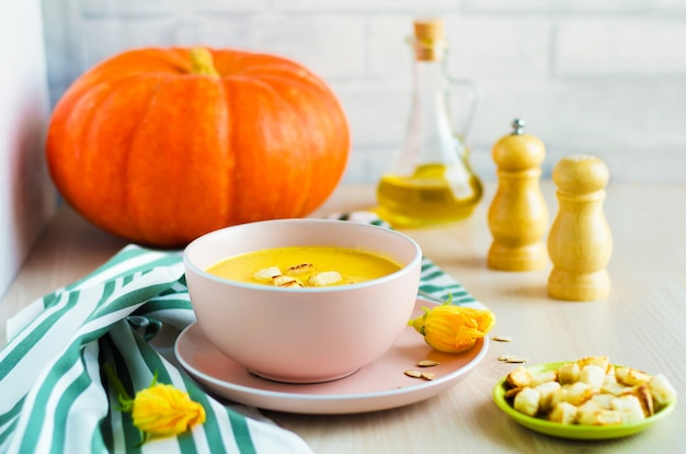 Creamy pumpkin soup with seeds and croutons in a bowl.