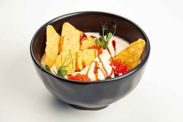 Creamy salmon soup in a black carriage