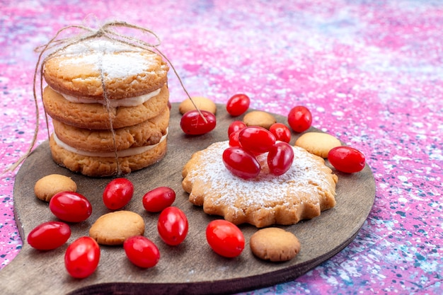 Сливочное печенье-сэндвич с красным кизилом на ярком бисквитном пироге с кисло-сладкими фруктами