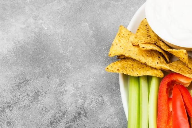 Сливочный соус в белой миске, различные овощи (сельдерей, перец) и начос. вид сверху, скопируйте пространство. пищевой фон