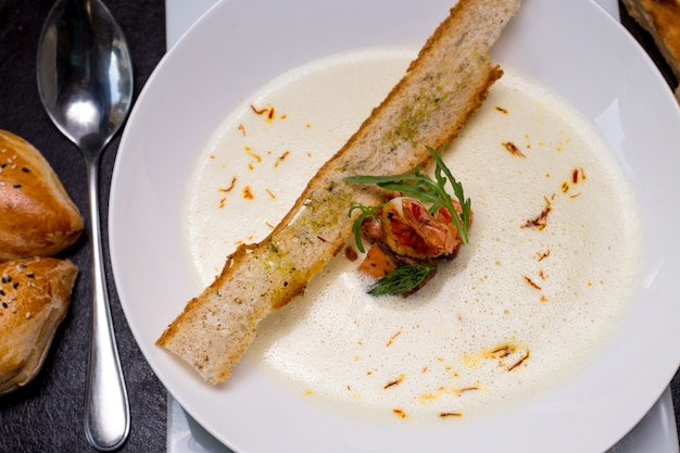 Creamy seafood soup prawns crackers buns saffron top view