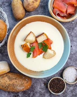 Ciotola di zuppa cremosa guarnita con ripieno di pane al salmone e prezzemolo