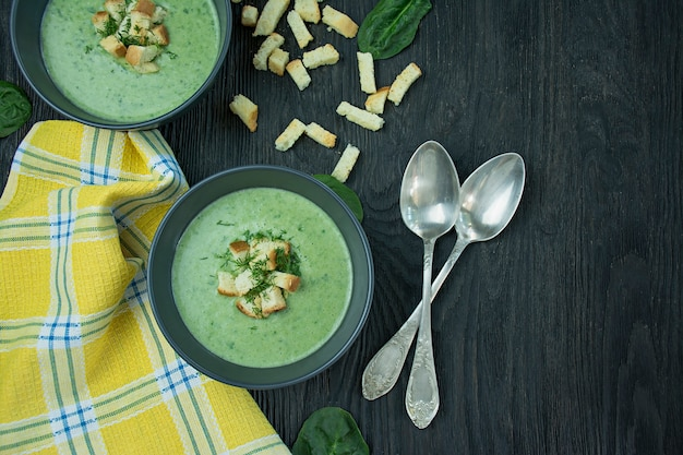 Creamy spinach soup with crackers, herbs and chia seeds. green soup served in a bowl on a wooden table. . flat lay.