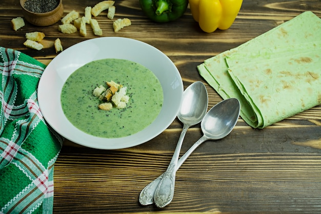 Creamy spinach soup with crackers, herbs and chia seeds