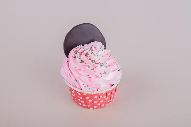 Creamy sweet cupcake on white surface