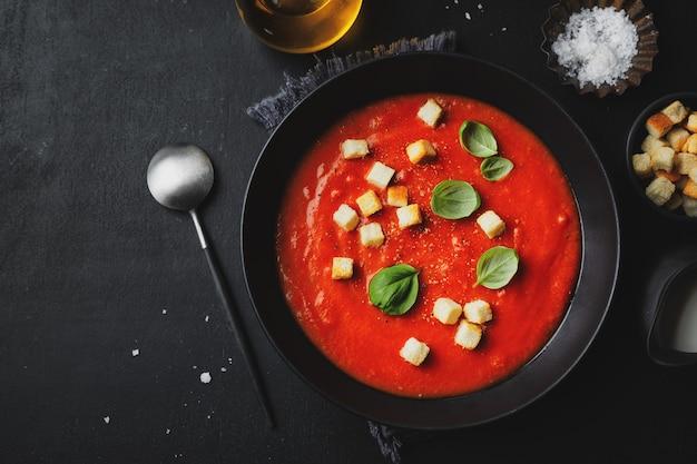 Сливочный вкусный томатный суп подается в миске на темном фоне. вид сверху.