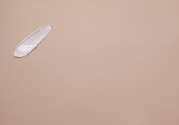 Сливочная текстура. мазок белого крема для рук на бежевом фоне.