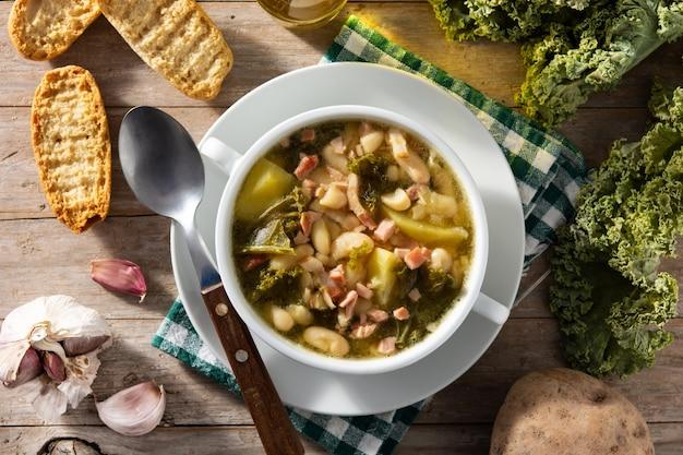 木製のテーブルのボウルにクリーミーなトスカーナのスープ。上面図