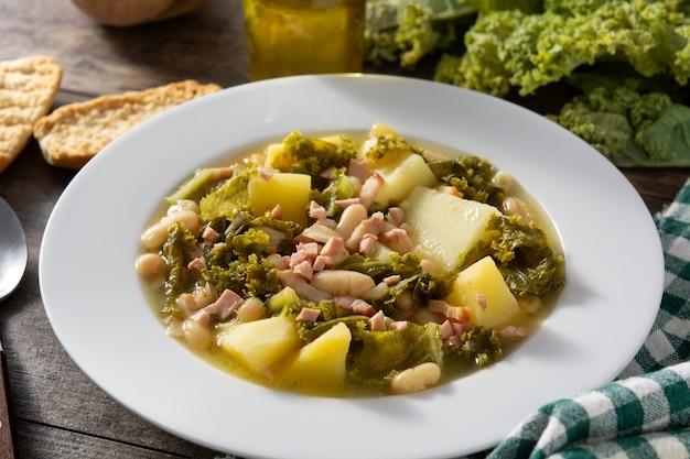 木製のテーブルのボウルにクリーミーなトスカーナのスープ