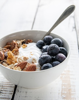 Creamy yogurt topped with granola and blueberries