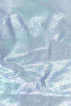 Creased textile texture, background template. shine fabric light blue drapery. sheene sharkskin fabrics for fashion dress. shiny fashion clothing material sample.
