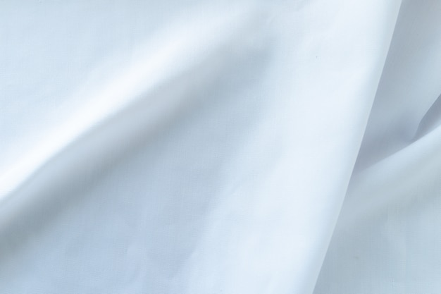 Creased white cloth material fragment as a background.