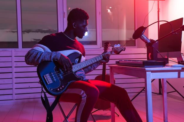 音楽とレコーディングスタジオのコンセプトを作成する-アフリカ系アメリカ人の男性ギタリストがエレクトリックベースを録音する