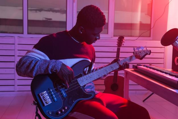 音楽とレコーディングスタジオのコンセプトを作成します。エレクトリックベースを録音するアフリカ系アメリカ人のギタリスト