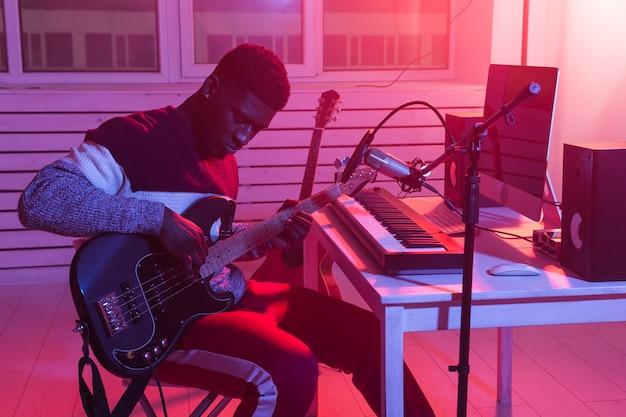 Создание музыки и концепция студии звукозаписи - гитарист афроамериканца записывает трек электрогитары в домашней студии