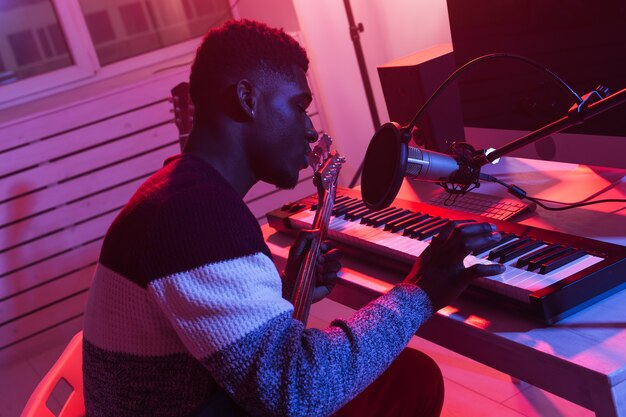 音楽とレコーディングスタジオのコンセプトを作成します。アフリカ系アメリカ人の男性ギタリストレコーディングシンセサイザー