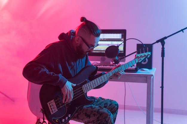 音楽とレコーディングスタジオのコンセプトを作成する-エレキギターを録音するひげを生やした面白い男のギタリスト