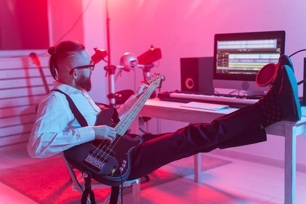 音楽とレコーディングスタジオのコンセプトを作成する-エレクトリックベースギターを録音するひげを生やしたギタリスト