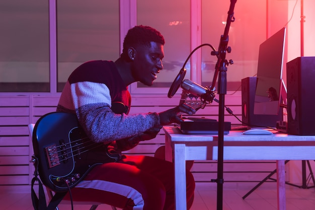 Создание музыки и концепция студии звукозаписи - гитарист бородатый мужчина записывает трек электрогитары в домашней студии.
