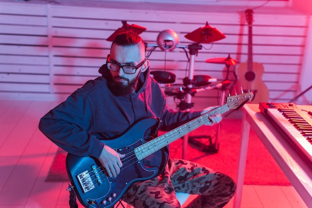 音楽とレコーディングスタジオのコンセプトを作成する-エレキギタートラックを録音するひげを生やしたギタリスト