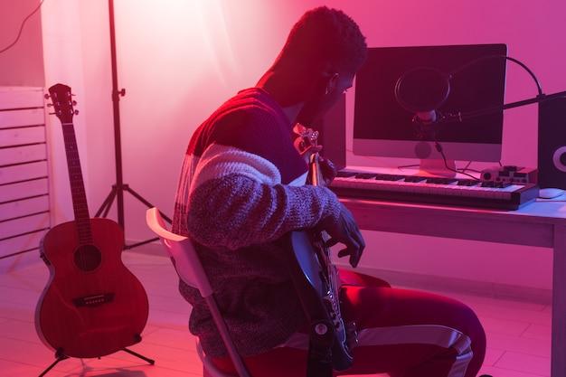 音楽とレコーディングスタジオのコンセプトを作成する-エレクトリックベースギターを録音する黒人ギタリスト