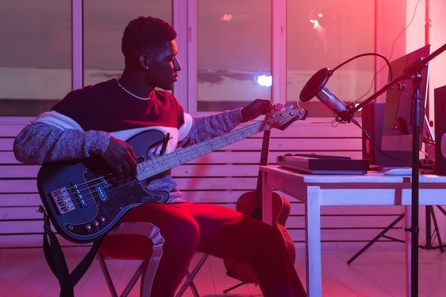 音楽とレコーディングスタジオのコンセプトを作成します。エレクトリックベースギターを録音する黒人ギタリスト