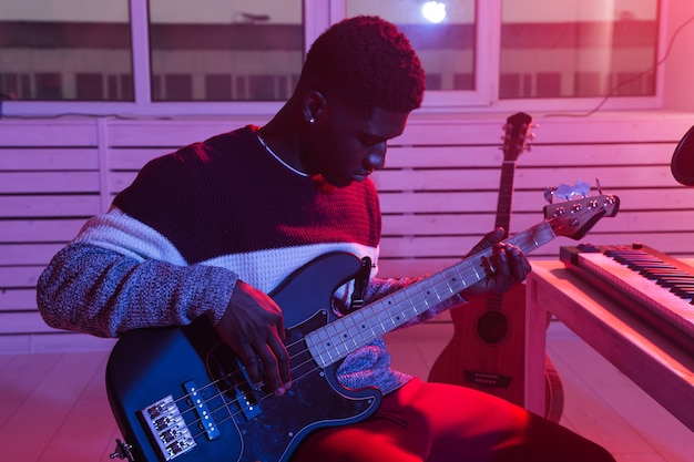 Create music and a recording studio concept. african american man guitarist recording electric bass