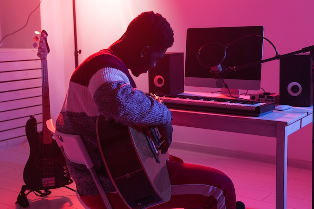 Create music and a recording studio concept - african american man guitarist recording electric