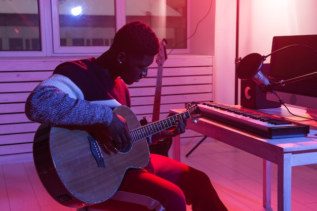 Create music and a recording studio concept. african american man guitarist recording electric