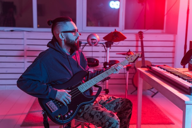 Create music and a recording studio concept. bearded funny man guitarist recording electric bass