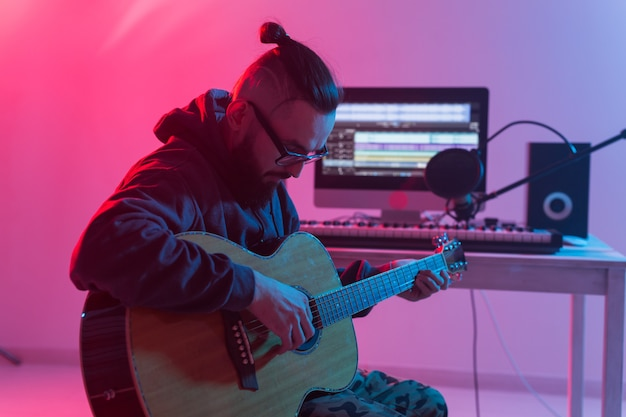 Create music and a recording studio concept. bearded funny man guitarist recording electric guitar