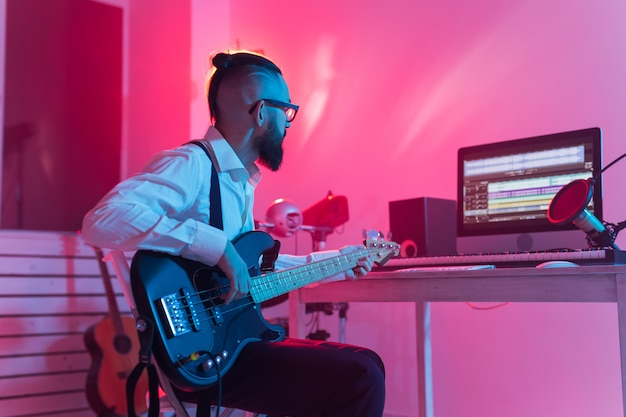 Create music and a recording studio concept. bearded man guitarist recording electric guitar track