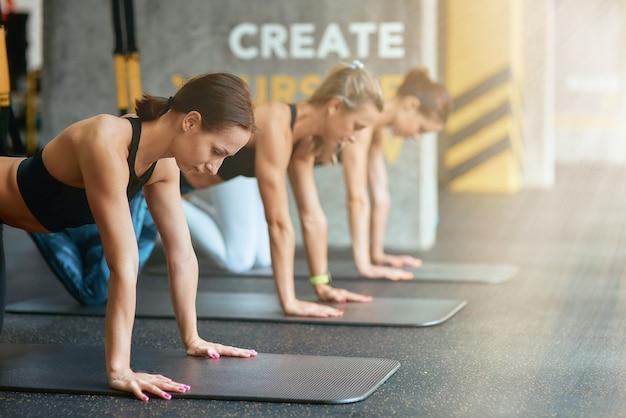 自分で作成します。ジムでtrxフィットネスストラップで運動している3人の若いスポーツ女性のグループ。サスペンショントレーニング、トレーニング、ウェルネス、健康的なライフスタイル