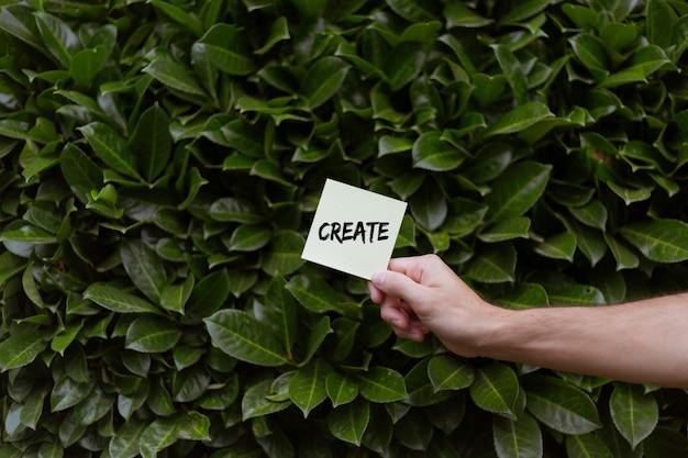 緑の月桂樹を背景に、createプリントの白いカードを持っている人