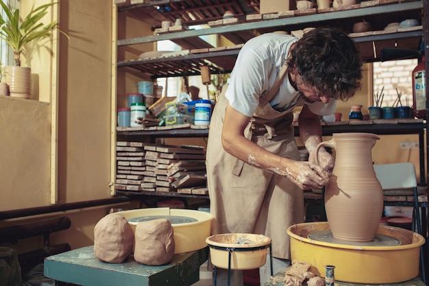 白い粘土のクローズアップの瓶または花瓶を作成します。マスター廃人。粘土の水差しマクロを作る男の手。ワークショップの彫刻家は、陶器のクローズアップから水差しを作ります。ろくろのツイスト。