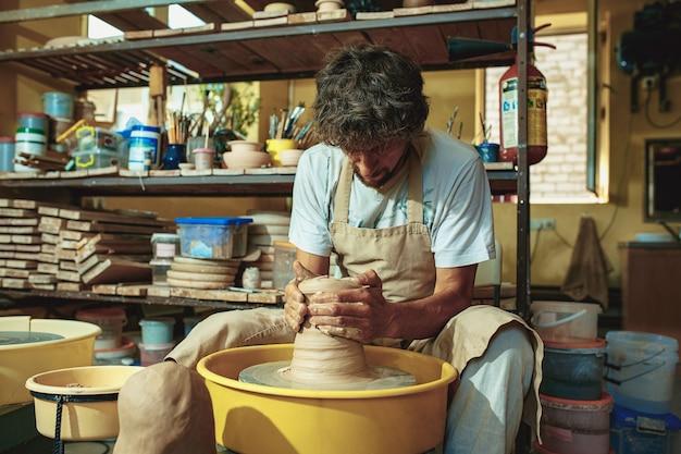 Создание кувшина или вазы из белой глины крупным планом. мастер черепок.