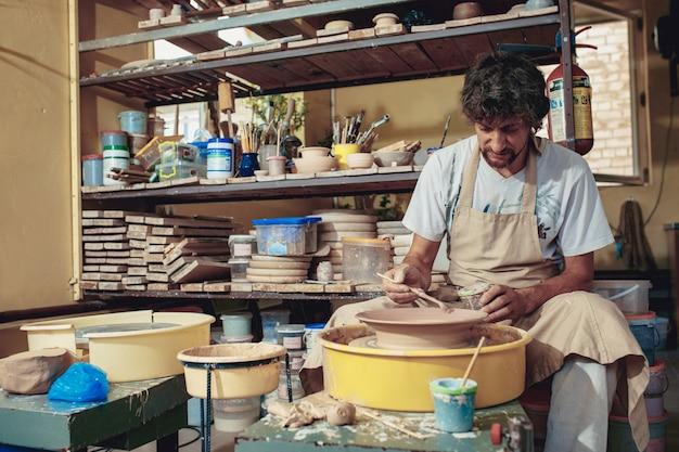 Создание банки или вазы из белой глины крупным планом.