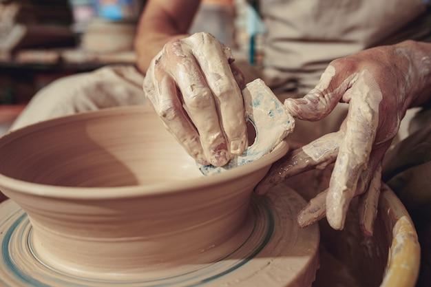 Создание кувшина или вазы из белой глины крупным планом.