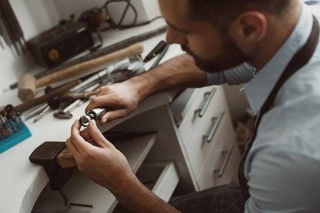 그의 작업대에서 새로운 은반지를 만드는 남성 보석상의 예술 근접 촬영 사진 만들기