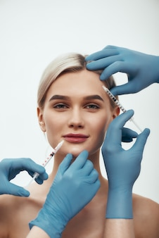 Creating beauty portrait of young pretty woman looking at camera and smiling while doctors in