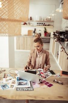Создание одежды. улыбаясь эскизы чертежа модельера сидя за столом с ее компьтер-книжкой.