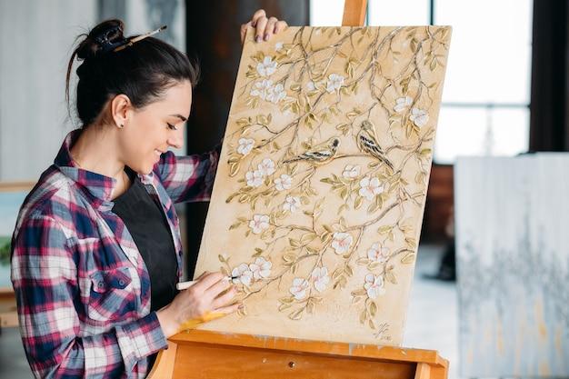 花柄のアートワークを作成します。アーティストの才能と想像力。モデリングツールを持つ女性画家。イーゼルのキャンバス。