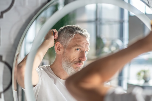 Creating a hairstyle. a man combing his hair in the morning