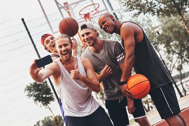 幸せな思い出を作る。スポーツウェアの若い男性のグループは、屋外に立っている間、自分撮りと笑顔を取ります
