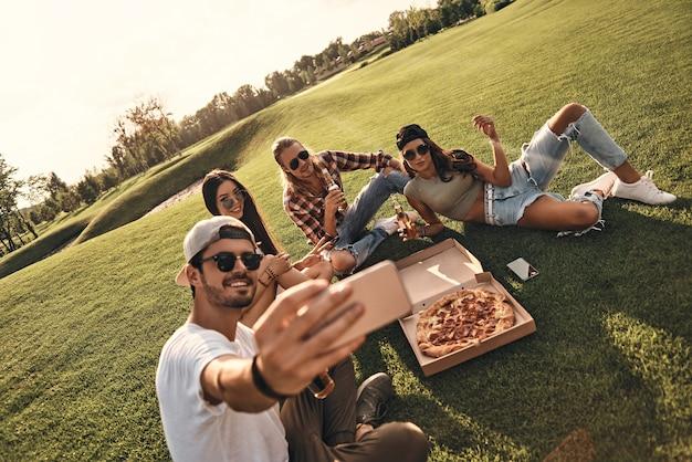 幸せな思い出を作る。屋外で食べ物や飲み物を楽しみながら自分撮りをしているカジュアルな服装で若い笑顔の人々のグループ