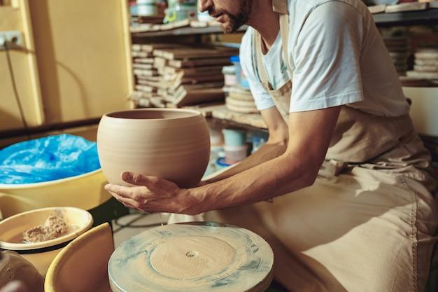 Creazione di un barattolo o vaso di primo piano di argilla bianca. maestro coccio. Foto Gratuite