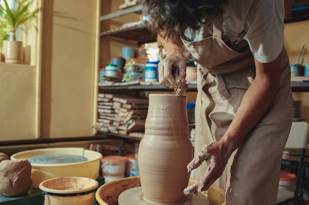Creating a jar or vase of white clay close-up.
