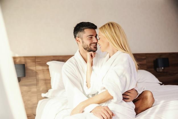 Создание воспоминаний в гостиничном номере, нежное прикосновение, полное любви. красивая улыбающаяся пара, милая блондинка и красивый мужчина в белых халатах. тепло объятий